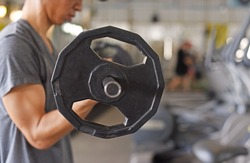 Weight training exercise for building muscle concept, close up hand of young man do exercise in biceps curl position with dumbbell in the gym