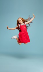 Weightless, freedom. Happy redhair girl in red dress on blue studio background. Looks happy, cheerful. Copyspace for ad. Childhood, education, emotions, facial expression concept. Jumping high, flying