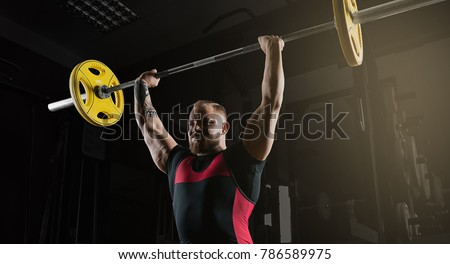 Weightlifter does an exercise with a barbell. Barbell above the head #786589975