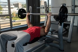 Weightlifter On Benchpress. Young Men In Gym Exercising On The Bench Press