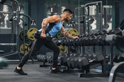 Weightlifting. Young bodybuilder taking dumbbells from equipment rack at gym, empty space