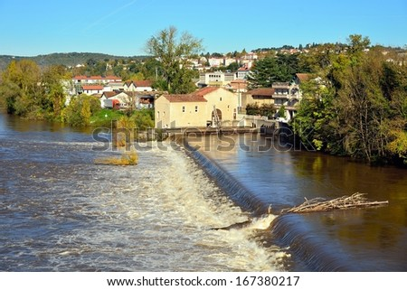 Weir on a river in flood and logjam, lot river in Cahors, France