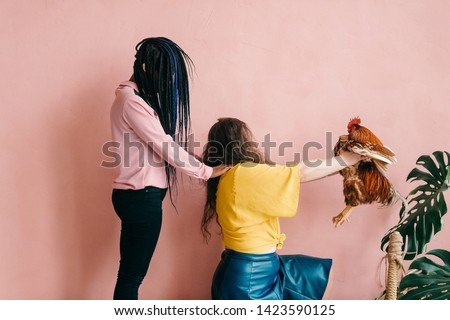 Weird and odd female interracial couple with hair covering their faces. African american girl holding hands on shoulders of her caucasian friend with chicken Stockfoto ©
