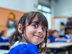 Weird face of elementary schoolgirl in classroom.