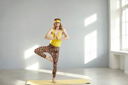 Weird fit guy in hilarious leopard leggings standing on gym mat and doing Tree pose. Funny young man in retro activewear practicing Vrikshasana yoga exercise at home. Balance and harmony humor concept