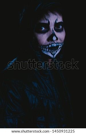 Weird man with skull face makeup on black background, portrait photography