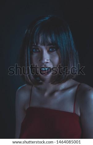 Weird woman with dark tone makeup on black background, portrait photograph