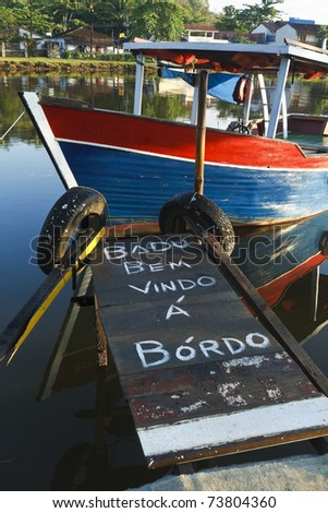 Welcome aboard message written in Portuguese on a gangplank leading to a wooden boat in Paraty, Brazil.