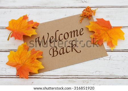 Welcome Back Card, A brown card with words Welcome Back over a distressed wood background with Autumn Leaves