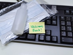 Welcome back note with hand sanitizer and mask on work keyboard; Back to work note with alcohol gel to prevent coronavirus / infection