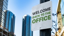 Welcome back to the office Worn Sign in Downtown city setting