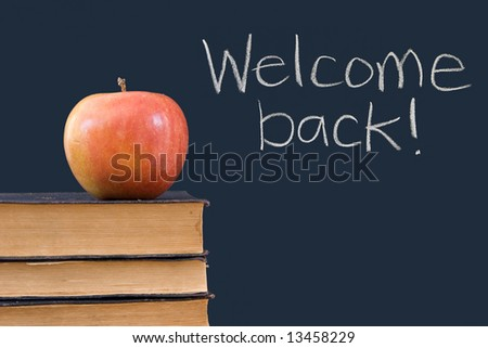 Welcome back! written on chalkboard with apple, books - stock photo