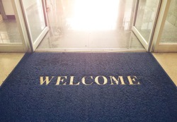 Welcome blue mat in front of door, shop