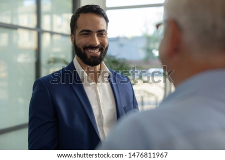 Welcome here. Cheerful bearded man keeping smile on his face while enjoying friendly conversation