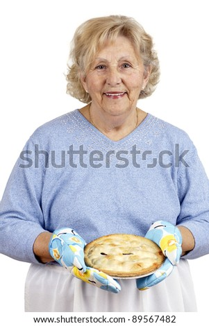 Welcome home concept: grandma is smiling while offering warm homecooked meat pie, wearing oven mitts.