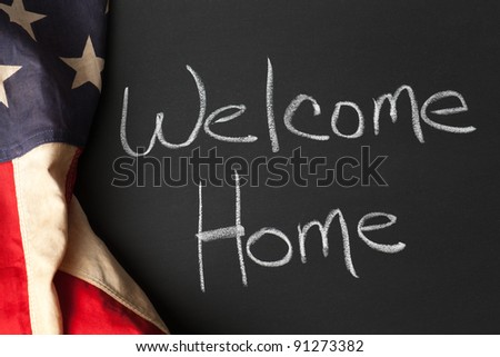 Welcome home sign on a chalkboard with vintage American flag