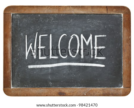 welcome -  hospitality concept - white chalk handwriting on isolated vintage slate blackboard