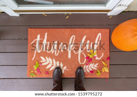 """Welcome mat on the front porch with the word """"thankful"""" with boots and fall leaves"""