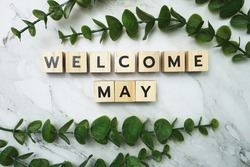 Welcome May alphabet letter with green leave flat lay on marble background