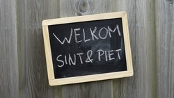 Welcome Santa and Pete written in Dutch on a chalkboard for Santa Claus