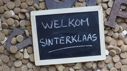 Welcome santa-claus written in Dutch on a chalkboard between ginger nuts