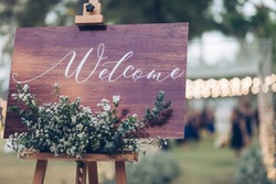welcome sign wood with flowers , rustic wedding sign  on blur background and bukeh