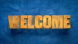 welcome sign - word in vintage letterpress wood type over blue handmade paper, hospitality concept