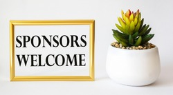 WELCOME SPONSOR words written on a golden photo frame, next to a cactus on a white background