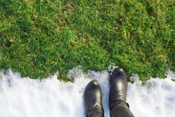 Welcome spring. Goodbye winter. Black woman boots standing on white melting  snow. Empty place for text, quote or sayings on green grass. Point of view shot. Closeup.