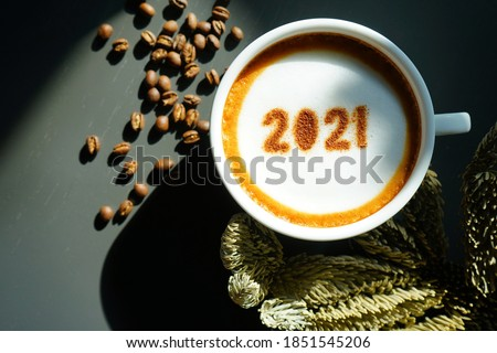 Welcome 2021 theme coffee cup with number 2021 on frothy surface flat lay on grey wooden table with coffee beans and dried pine branches. Happy new year 2021, Holidays food art concept. (close up)
