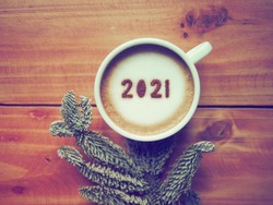 Welcome 2021 theme coffee cup with number 2021 on frothy surface flat lay on wooden table background with dried pine branches. Happy new year 2021, Holidays food art concept. (close up, top view)
