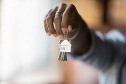 Welcome to new house. Close up of young african american man hand hold bunch of keys. Cropped shot of black guy real estate agent realtor give offer you client key from home flat apartment. Copy space
