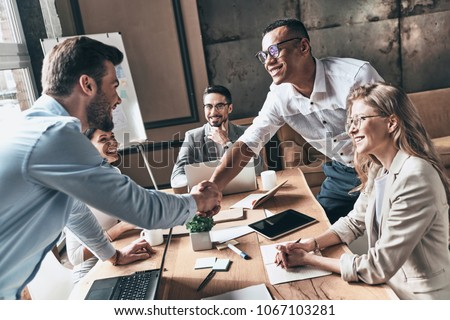Welcome to our team! Top view of young modern men in smart casual wear shaking hands while working in the creative office