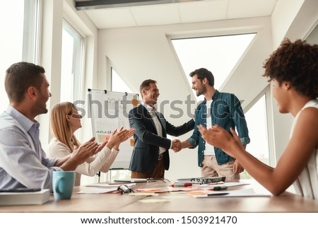 Welcome to our team Two cheerful colleagues shaking hands and smiling while having a meeting in the modern office