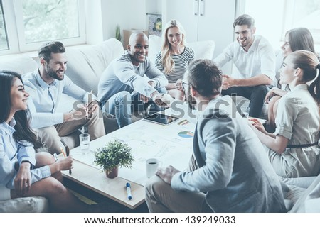 Welcome to team! Group of confident business people sitting around the desk together while two men shaking hands and smiling