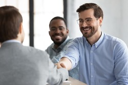 Welcome to team! Two friendly smiling male hr employers of diverse races satisfied by job interview result hiring young man applicant, greeting him and shaking hand glad to see as new member of staff