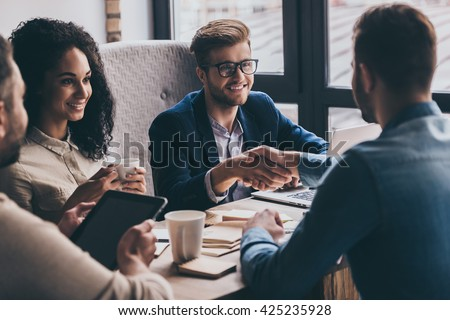 Welcome to team! Two men shaking hands and looking at each other with smile while their coworkers sitting at the business meeting  #425235928