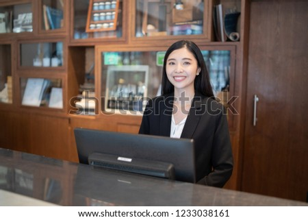 Welcome to the hotel,Happy young Asian woman hotel receptionist worker smiling standing at a Modern luxury  reception counter waiting for guests getting key card in hotel inn motel, lodge, hostel #1233038161