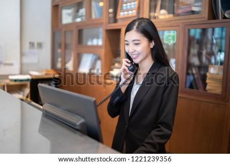 Welcome to the hotel,Happy young Asian woman hotel receptionist worker smiling standing,she taking  telephone call at a Modern luxury reception counter waiting for guests getting key card in hotel    #1221239356