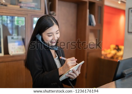 Welcome to the hotel,Happy young Asian woman hotel receptionist worker smiling standing,she taking  telephone call at a Modern luxury reception counter waiting for guests getting key card in hotel    #1236176194