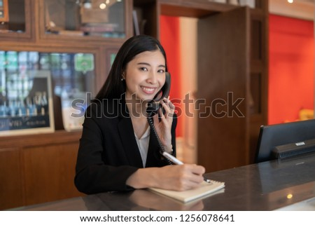 Welcome to the hotel,Happy young Asian woman hotel receptionist worker smiling standing,she taking  telephone call at a Modern luxury reception counter waiting for guests getting key card in hotel    #1256078641