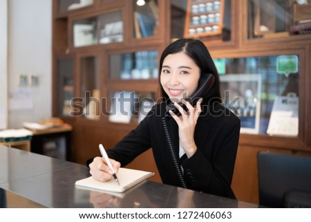 Welcome to the hotel,Happy young Asian woman hotel receptionist worker smiling standing,she taking  telephone call at a Modern luxury reception counter waiting for guests getting key card in hotel    #1272406063