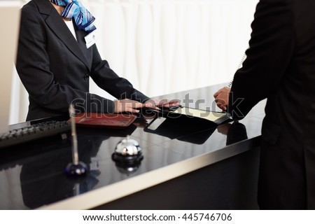 Welcome to the hotel. Male and female receptionists standing at the front desk