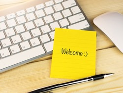 Welcome with smily face on sticky note on work table