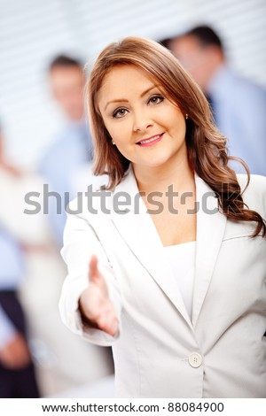 Welcoming business woman wit her hand extended ready to handshake