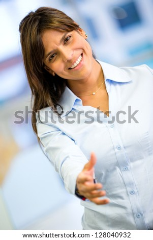 Welcoming business woman with hand extended to handshake