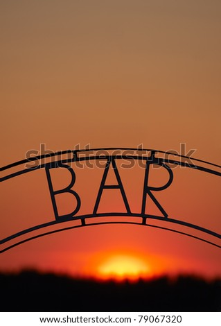 Welded iron bar sign in front of northern midnight sun