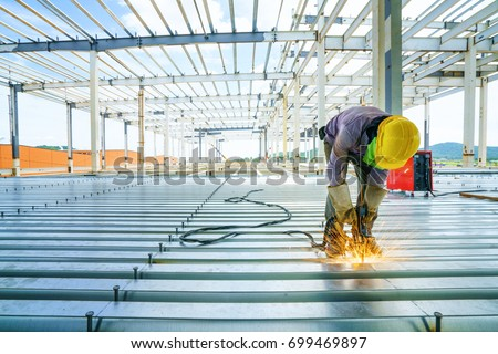 Welder are welds re-bar shear keys metal deck slab of mezzanine floor under the construction building in the factory with blue sky