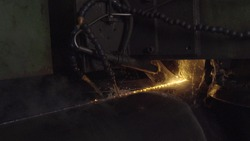 Welder complete with personal protective equipment is perform pipe welding in dark area using Automatic Welding System. Welding sparks spreading everywhere. Automat welding pipe production