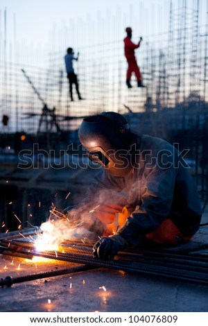 Welder does the job.Workers erecting steel in the background